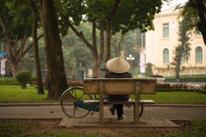 man sitting on bench with bike