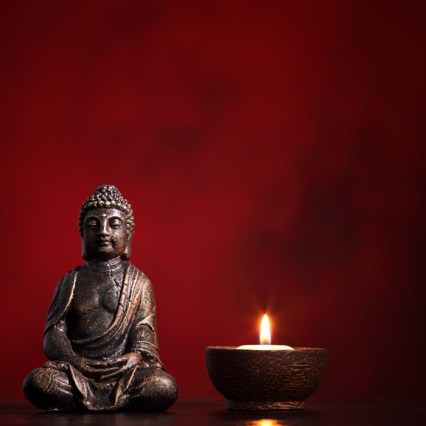 buddha-with-burning-candle-red-background